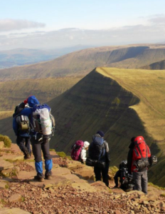 Participants walking down a steep mountain in the Brecon Beacons